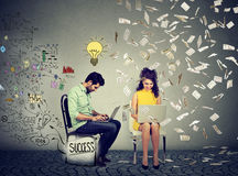 Умный человек работая на компьютере производит идеи рядом с женщиной используя компьтер-книжку под дождем денег Стоковое фото RF