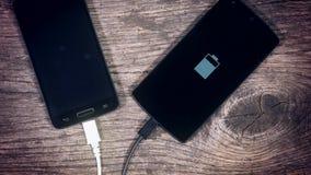 2 умных телефона поручая на предпосылке древесины grunge Состояние на экране акции видеоматериалы