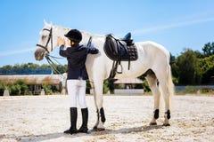 Умоляющая темн-с волосами женщина стоя около белой лошади седловины стоковое изображение rf