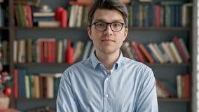 Университет библиотеки книжных полков студента молодого человека портрета усмехаясь сток-видео