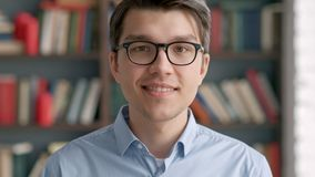 Университет библиотеки книжных полков студента молодого человека портрета усмехаясь видеоматериал