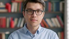 Университет библиотеки книжных полков студента молодого человека портрета усмехаясь акции видеоматериалы