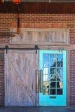 Уникальный деревенский вход двери амбара к построению с отражением природы в одной стороне со стеклянными форточками совсем устан стоковое фото