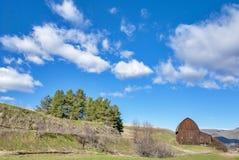 Уникально старый амбар в поле с голубым небом с облаками Стоковая Фотография RF