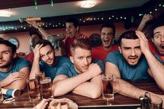 Унылая голубая команда дует на баре в баре спорт при красные вентиляторы команды празднуя и веселя в предпосылке Стоковая Фотография RF