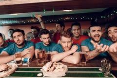 Унылая голубая команда дует на баре в баре спорт при красные вентиляторы команды празднуя и веселя в предпосылке Стоковые Изображения