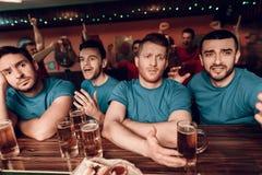 Унылая голубая команда дует на баре в баре спорт при красные вентиляторы команды веселя в предпосылке Стоковые Фото