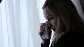 Унылая девушка около окна плачущ и думающ о что-то движение медленное сток-видео