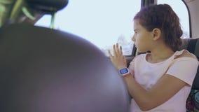 Унылая девушка пробурила сидеть в автомобиле в заднем перемещении места движения маленькая девочка пробуренная в автомобиле путеш акции видеоматериалы
