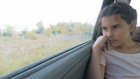 Унылая девушка пробурила сидеть в автомобиле в перемещении движения заднего сиденья маленькая девочка пробуренная в образе жизни  акции видеоматериалы