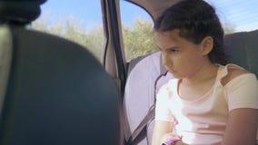 Унылая девушка пробурила сидеть в автомобиле в перемещении заднего сиденья маленькая девочка пробуренная в автомобиле путешествие акции видеоматериалы