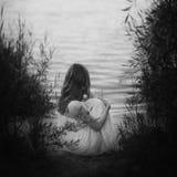 Унылая девушка сидя на песчаном пляже на свете захода солнца около озера вакханические стоковые изображения