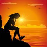 Унылая девушка сидя на скале смотря на море Стоковая Фотография RF