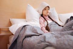 Унылая девушка сидя с полотенцем на ее голове Стоковые Фото