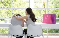 Унылая женщина сидя в комнате Друзья не дают вверх Унылая девушка и поддерживая друзья для того чтобы разрешить проблему стоковые изображения