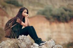Унылая женщина сидя на скалистой скале ужаснутой высот стоковые фотографии rf
