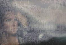 Унылая женщина смотря через окно с падением дождя в автомобиле Сторона молодой женщины за окном автомобиля дождя стоковые изображения