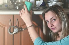 Унылая и утомленная девушка надеванная наручники к счетчику кухни с много стоковое фото