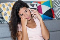 Унылая кавказская женщина получая плохую новость на телефоне Стоковая Фотография