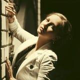 Унылая красивая женщина моды стоя на стене в ноче стоковые фото