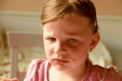 Унылая милая малая девушка Малая девушка смотрит уныло Малая девушка сидит в кухне Стоковая Фотография RF