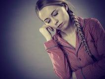 Унылая молодая женщина подростка сидя на кровати стоковая фотография