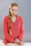 Унылая молодая женщина подростка сидя на кровати стоковое изображение