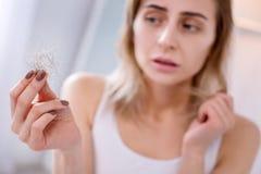 Унылая несчастная женщина смотря ее волосы стоковые фото