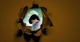 Унылая огорченная женщина держа руки в стороне через сюрреалистическое бумажное отверстие Стоковое Фото