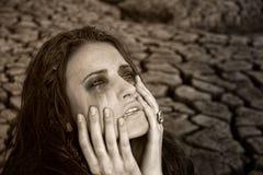 Унылая пакостная женщина на треснутой пустыне земли Стоковые Изображения RF