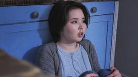 Унылая сиротливая молодая азиатская девушка сидя на поле в кухне, держа ее колени с оружиями, концепция 50 насилия в семье видеоматериал