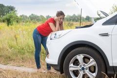 Унылая склонность женщины на сломленном автомобиле в поле и смотреть двигатель Стоковое Фото