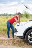 Унылая склонность молодой женщины на сломленном автомобиле в поле и ждать помощи Стоковые Изображения RF