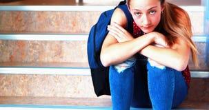 Унылая школьница сидя самостоятельно на лестнице сток-видео