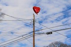 Унылое фото красного воздушного шара сердца вставило на проводах телефона Стоковое Фото