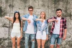 Унылые и несчастные молодые человеки и женщины стоят совместно на серой предпосылке и смотрят на камере Они показывают Стоковые Фотографии RF