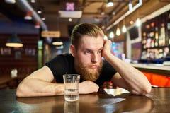 Унылый бородатый человек получая пьяный в баре стоковая фотография