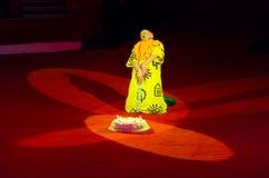 Унылый клоун сидит на арене около большого именниного пирога с горящими свечами Стоковая Фотография