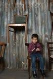 Унылый мальчик в checkered усаживании рубашки стоковое фото rf