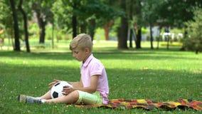 Унылый мальчик сидя в парке и бросая шарике, недостатке друзей, жертве задирать акции видеоматериалы