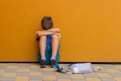Унылый один мальчик сидя около красочной стены outdoors стоковая фотография rf