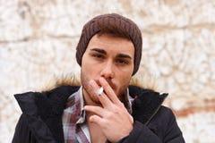 Унылый парень при шляпа шерстей куря сигару стоковая фотография rf