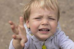 Унылый плача малыш вытягивает его руки вверх Закройте вверх по портрету ребёнка прося выберите вверх стоковые изображения rf