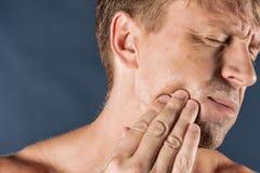 унылый подавленный человек в боли держа его щеку Портрет человека на голубой предпосылке Выражение лица эмоции чувства и люди стоковая фотография rf