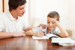 Унылый сынок делает домашнюю работу стоковое изображение