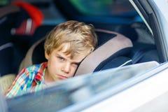 Унылый утомленный мальчик ребенк сидя в автомобиле во время затора движения Стоковое фото RF