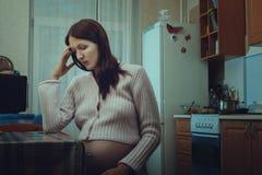 Унылая беременная женщина сидя в кухне стоковые фотографии rf