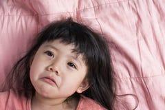 Унылая девушка Азии младенца на кресле в пинке стоковая фотография