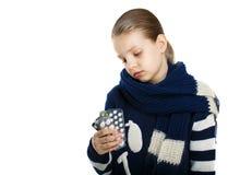 Унылая девушка в теплых свитере и шарфе держа таблетку в руках стоковые изображения
