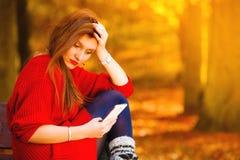 Унылая девушка осадки с мобильным телефоном в парке осени Стоковое Изображение